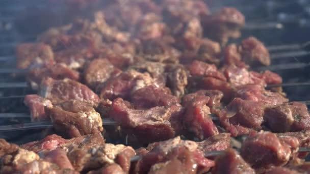 Chutné šťavnaté vepřové kotlety vaření na kovové špízy na dřevěném uhlí gril s kouřem. Detail pohledu, selektivní zaměření na chutné kousky masa.