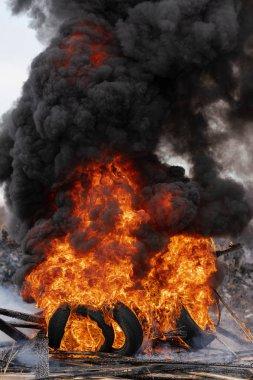 Yanan otomobil lastikleri, kırmızı ateşin güçlü alevi ve gökyüzündeki siyah duman bulutları