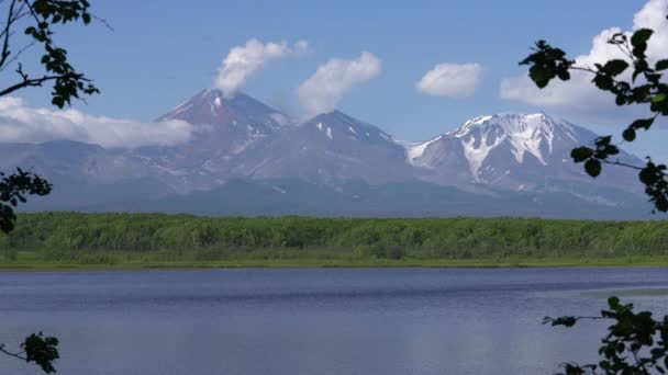 Úchvatný pohled na kužel aktivní sopky Avačinskaya sopka, odraz hory v malebném alpském jezeře a mraky plující přes modrou oblohu nedaleko hor. Letní krajina na poloostrově Kamčatka.