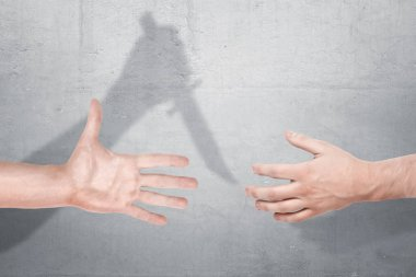 Two male hands getting close for a handshake with a shadow of one hand holding a knife on a concrete background.
