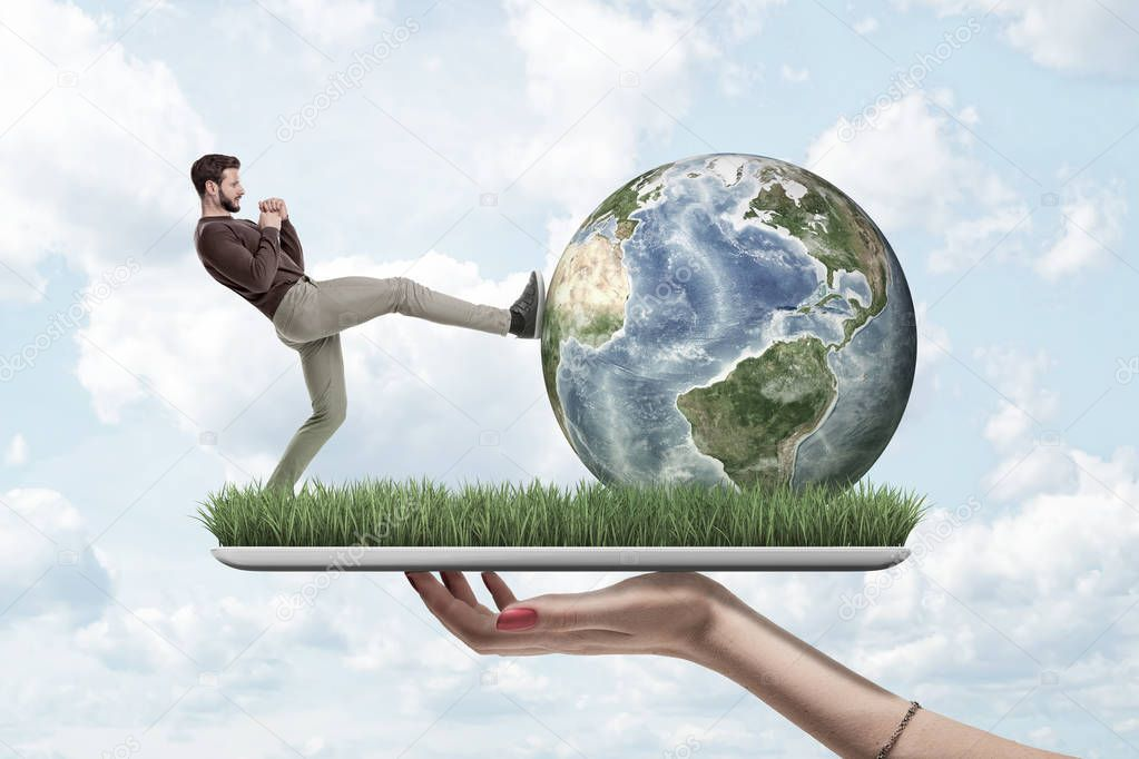 Side view of man in casual clothes kicking Earth globe, on top of digital tablet screen covered with green grass, held in womans hand.