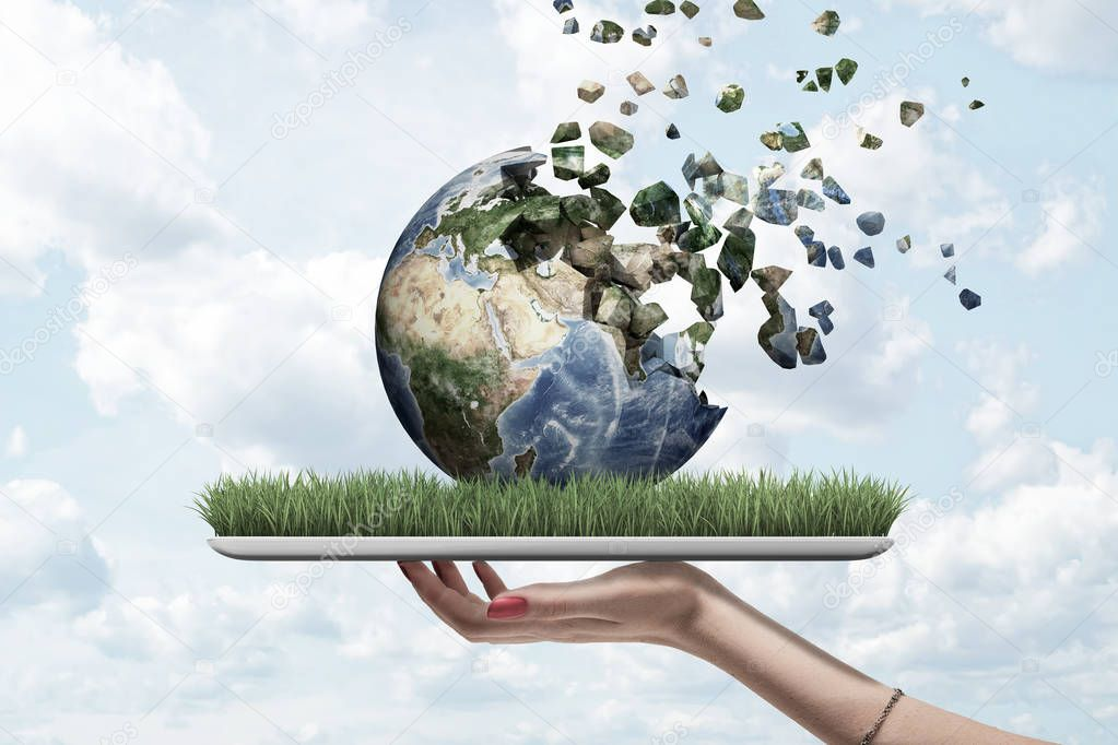 Side view of womans hand holding tablet with green grass on screen and Earth globe on top which is dissolving into pieces that float away into sky.