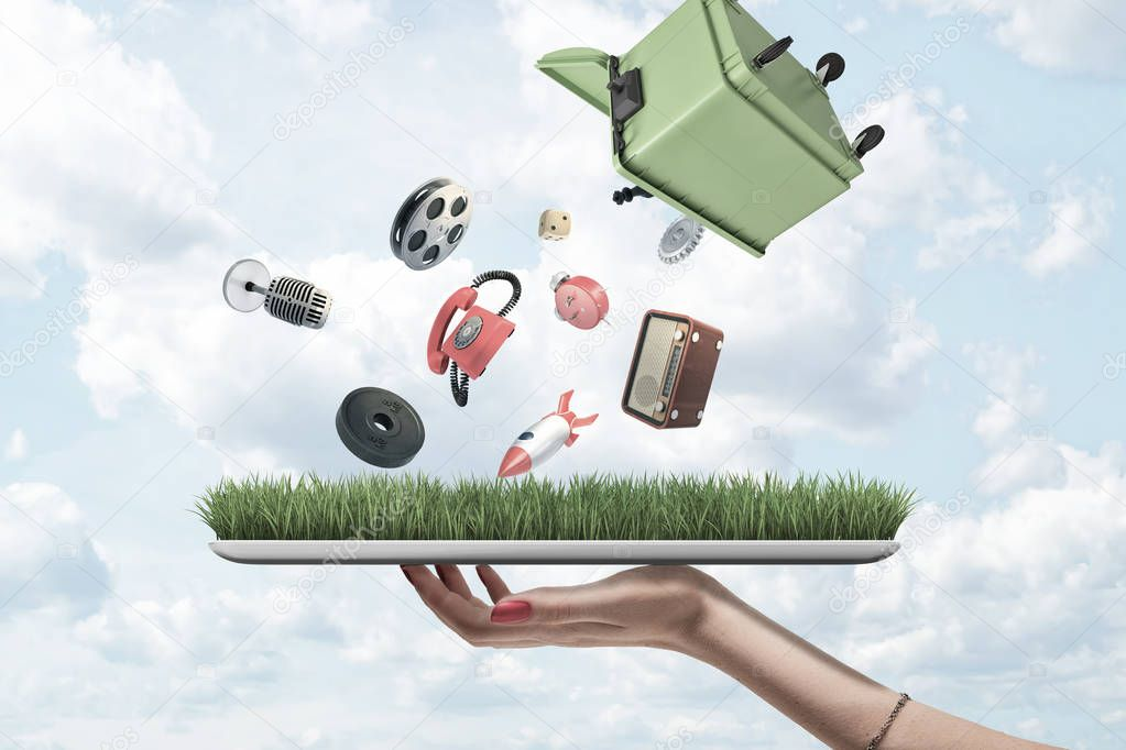 Side view of womans hand holding tablet with green grass on screen and green dumpster upside down in air out of which misc objects are falling.