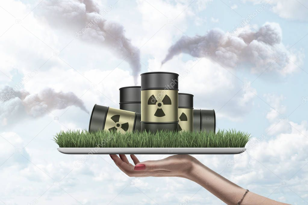 Womans hand holding ipad with green grass growing on screen and pile of radioactive waste barrels on it puffing clouds of smoke all around.