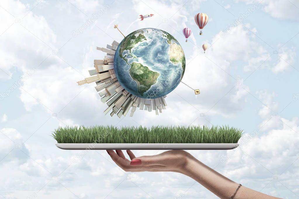 Crop side view of womans hand holding digital tablet with grass on screen and little Earth above with skyscrapers on and hot-air balloons flying around.