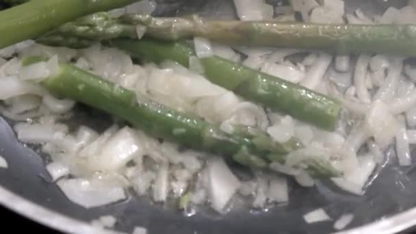 chef is cooking asparagus with onions in the pan