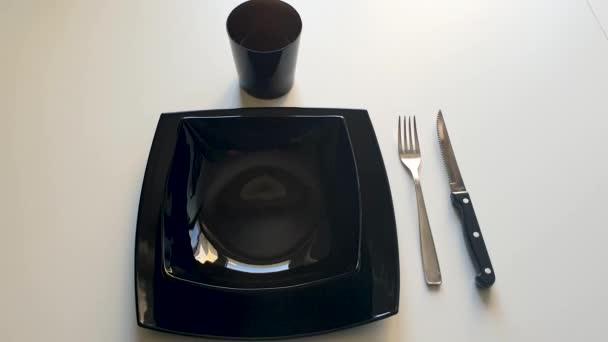 Černá sada stolů složená z černých talířů, stříbrné vidličky a černého nože na bílém stole