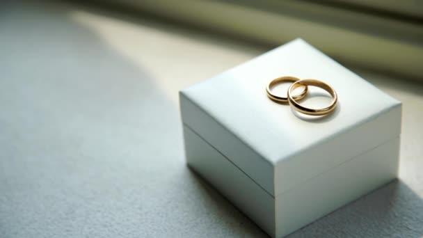zlaté snubní prstýnky na dřevěné bedně