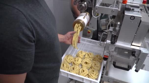 Person making spaghetti and pasta using a pasta machine
