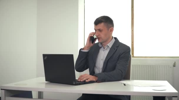 Adult businessman talking on phone in office