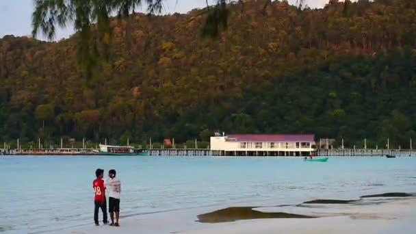 Two Cambodian mans walking on the paradise beach at Koh Rong Samloem island. Sunset with beautiful light in the distance. 17 September 2017 Cambodia, Asia.