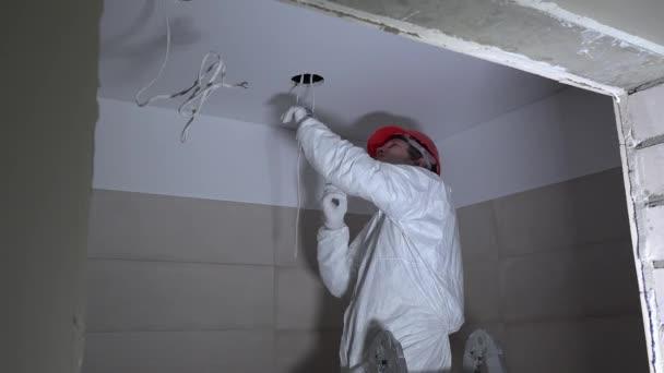 Homme faisant trou de plâtre du plafond pour une installation électrique.