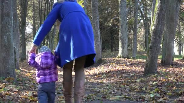 mother walk with little baby in autumn park with dry leaves. 4K