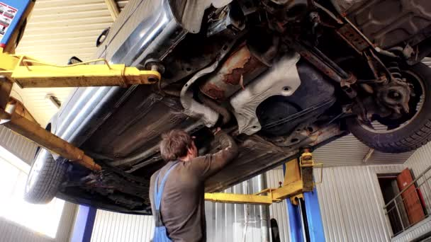 Auto mechanics working under the car hanging on lift.