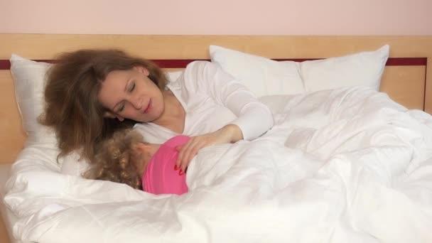 Milující maminka pohladit její dítě holka ležící v posteli a aby se usnout