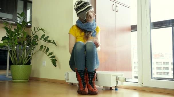 heiße Frau entkleiden Mütze und Schal sitzt auf Heizkörper. Temperatur steigt.