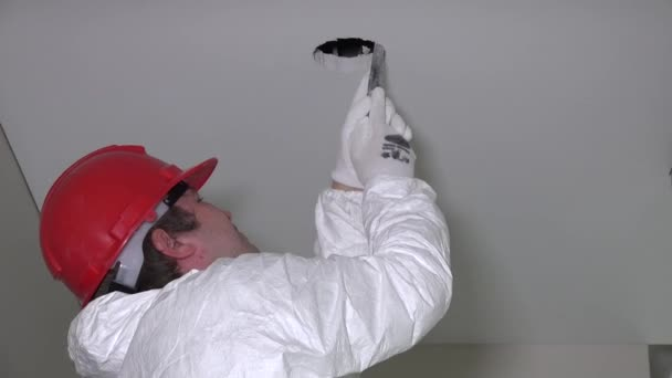 Professional worker man make drywall ceiling holes for lighting installation and climb down from ladder. Zoom out shot. 4K UHD