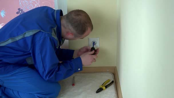 Electrician man with screwdriver indicator test voltage on outlet socket.