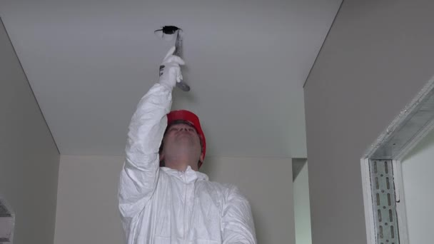 Professional worker in work wear make drywall ceiling holes for light install