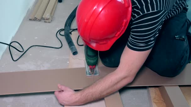 Man cutting laminate flooring with electric hand saw.