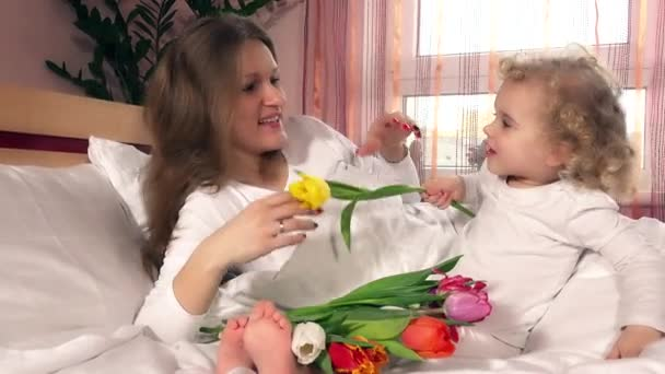 Lovely mom and child girl with bouquet of tulip flowers in bed at home
