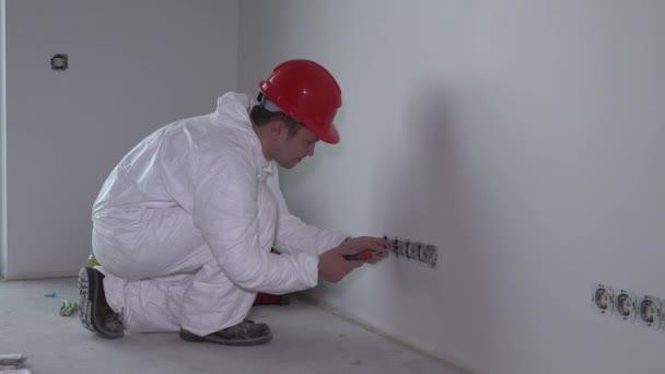Muž elektrikář s šroubovák oprava zásuvky zásuvky zdi připojit v novém domě