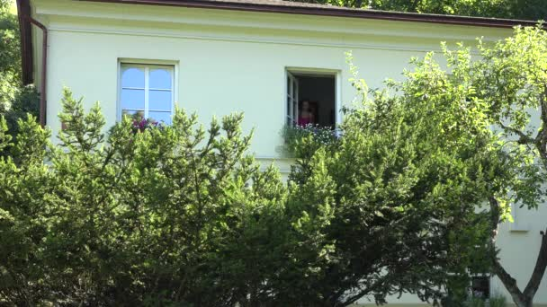 Weibliche Haus Halter offen Fenster und Wasser Blumentöpfe auf der Fensterbank im Obergeschoss des Hauses. Zeigen Sie durch Tau Busch an. Statische Schuss. 4k