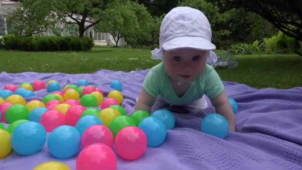 Cute baby girl with white hat crawl between colorful balls on plaid. 4K