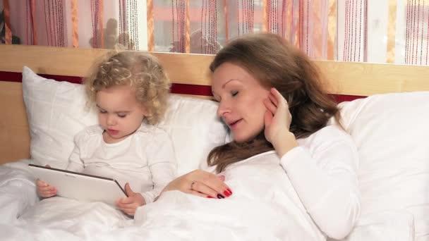 Nő fáradt gyönyörű anya elaludna szoláriumozás közben lánya néz tabletta számítógép