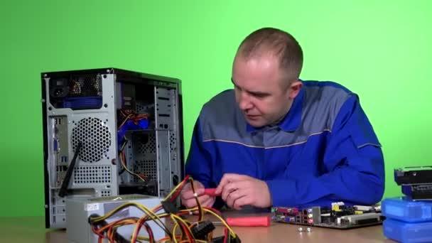 Mann repariert Desktop-Computer bei der Arbeit