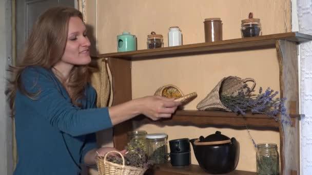 Herbalist woman prepare dried herbs in wicker baskets for winter time. 4K