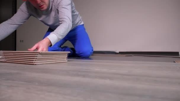 Profesionální zaměstnanci pokládání dřevěné dub laminodesek na podlaze v nové místnosti