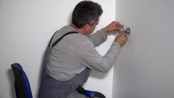 Electrician man with screwdriver connect electrical socket to wires
