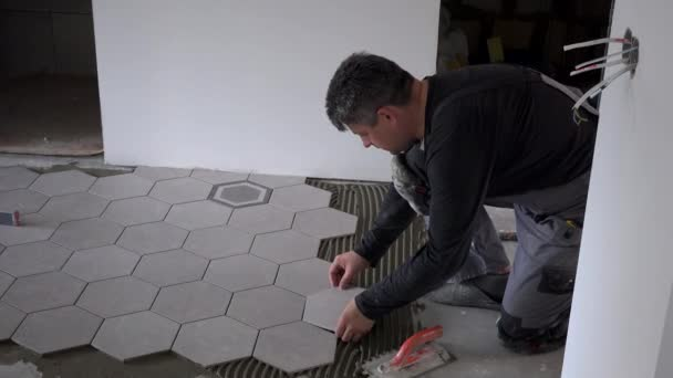 Close look at construction worker laying down hexagon tiles on cemented floor