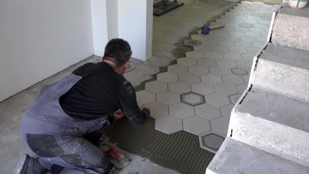 Stavební pracovník položil na podlahu šestiúhelné dlaždice. TILER instalovat kameny z kameniny
