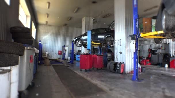 Dvě auta zvednuté v malé servisní stanici a mechanik opravit jedno auto.