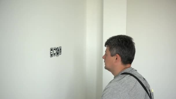Electrician man repair an electrical outlet socket in apartment