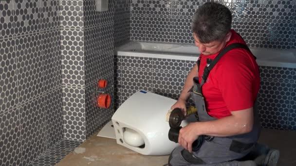 Instalatér sekat trubici s úhlovou brukou pro zavěšení záchodové mísy