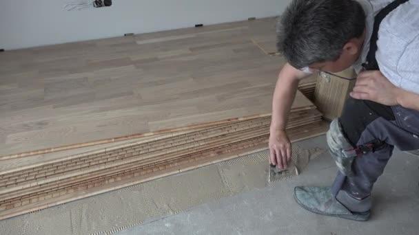 Muž s stěrkou naneste na betonovou podlahu lepivé dřevo