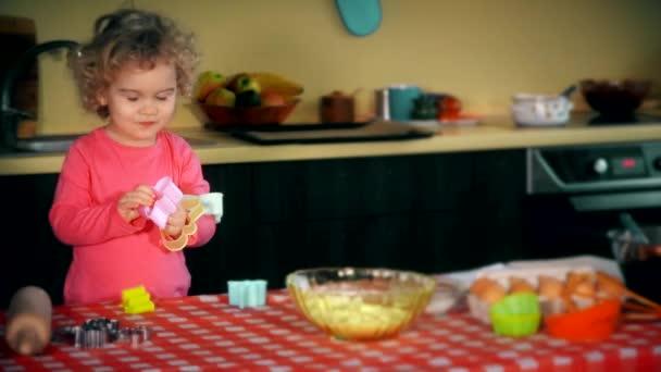 Legrační kluk, co si hraje s barevným koláčem. Děvče vypadá zvědavé.