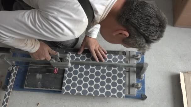 Stavební pracovník pracuje se zařízením na řezání podlahových dlaždicemi
