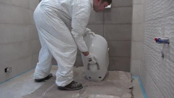 Junge Handwerker bringen Toilettenschüssel ins neue Bad. Bauindustrie