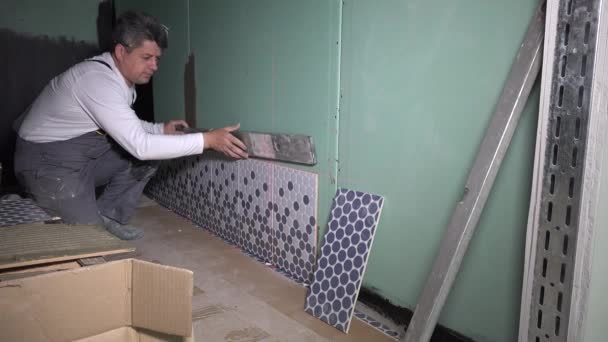 Ceramist check level of wall with leveling tool