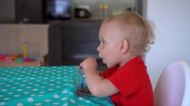 Portrét šťastného chlapečka se sklenicí džusu sedícího u stolu. Gimbalův pohyb