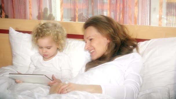 matka a malá kudrnatá dcera hrají herní video na tabletu v posteli. Dětství. 4K
