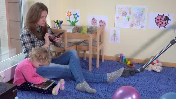 Mutter und Tochter spielen mit Tablet-Telefonen. Vater Staubsauger Wohnzimmer. 4K