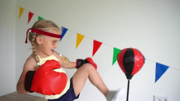 Kleines Mädchen schlägt Boxsack mit Bein 4-jähriges Kind mit Boxhandschuhen