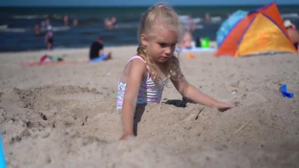 A fürdőruhás kislány befedi a testét homokkal. Homályos emberek