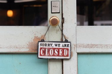 sorry we are closed sign hanging outside a restaurant, store, of
