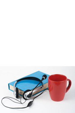 Headphones over blue hardback book with cup on white background